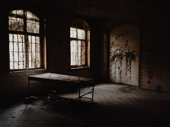 An old operating table with grooves to let bodily fluids (i.e. blood) leak down