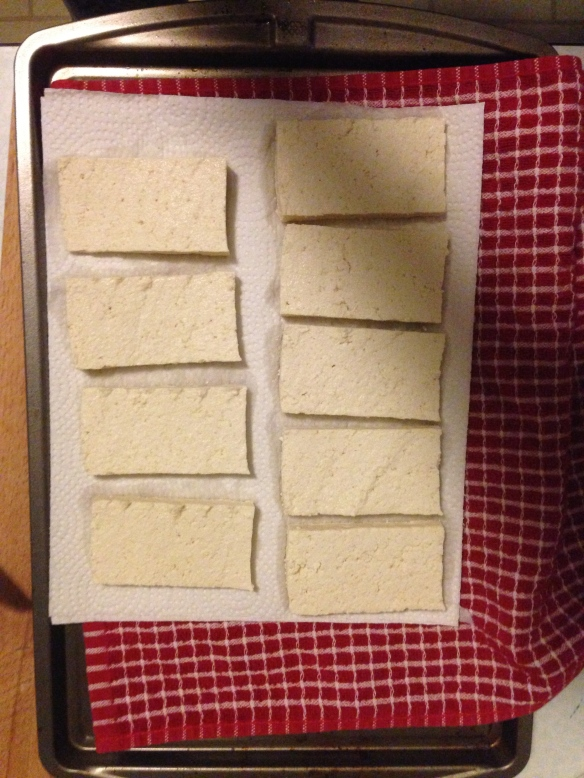 Put down a cloth towel on a hard surface (I use a baking sheet) and lay paper towels three thick on top. Place the tofu slices on top of the paper towels.