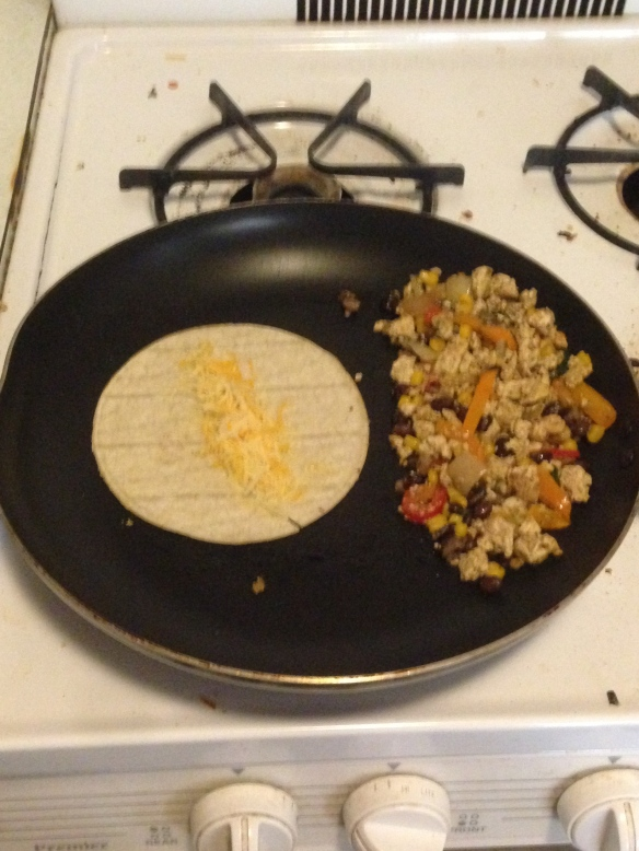 Clear the pan (or use a new one). Take a corn tortilla and cook it on one side for a minute or so before flipping. Add cheese and cook until the other side starts to brown and the cheese begins to melt.